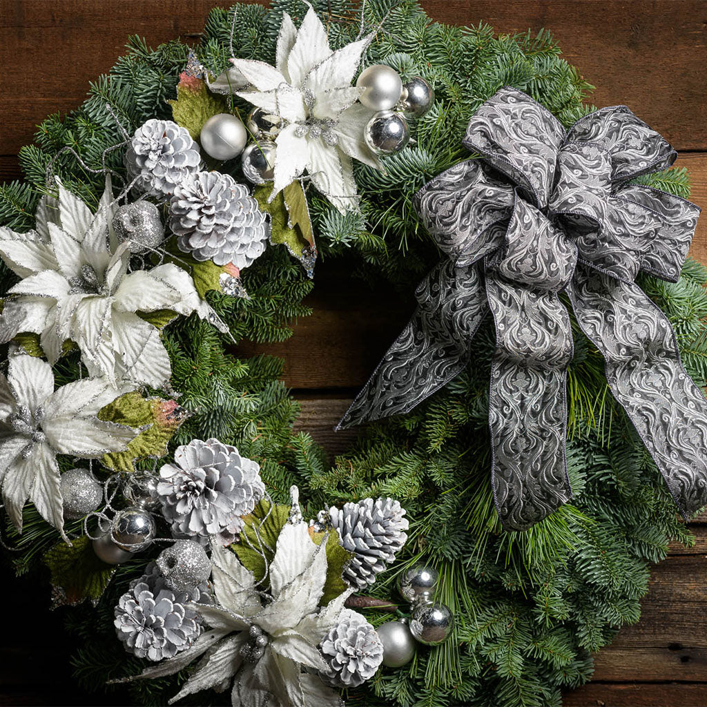 Christmas wreath noble fir pine with 4 white poinsettia flowers 4 of silver balls pine cones and a pewter grey bow