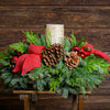 Holiday centerpiece with pine cones, red balls and red burlap bows topped with a birch log LED candle