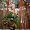 Fresh Evergreen wreath held by little girl pine cones antlers magnolia leaves and bronze ball clusters