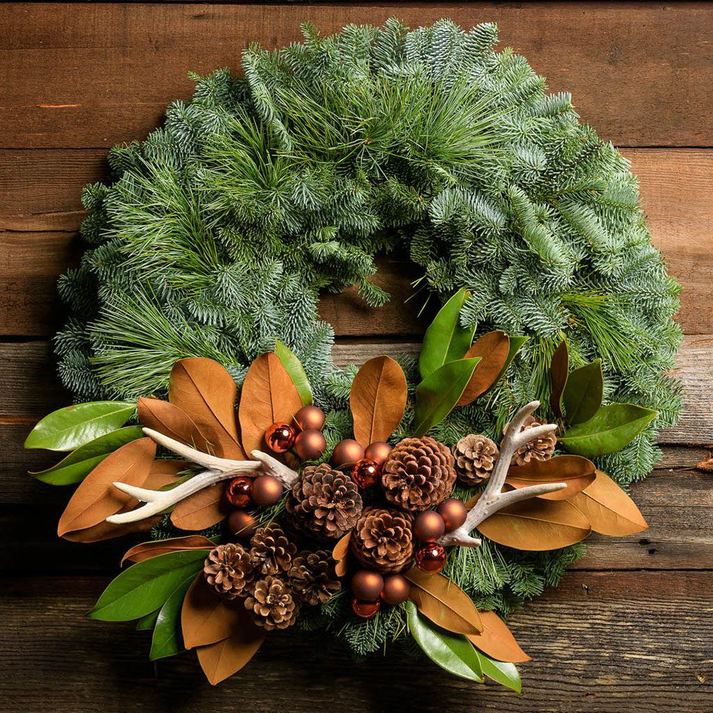 Fresh evergreen wreath made with fir and pine, pine cones antlers magnolia leaves and bronze ball clusters