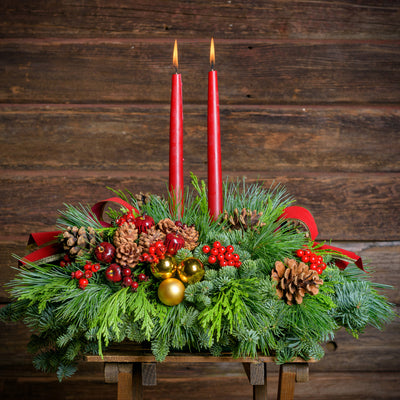 Traditional centerpiece with red balls, pine cones and berries with 2 red velveteen bows and two red taper candles