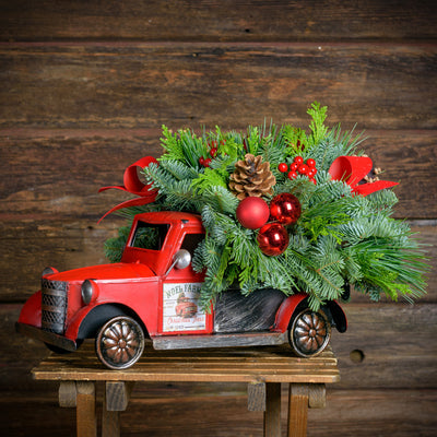 "Fresh greens, pine cones,red ball & berry clusters,red velvet bow tucks in a metal truck with removable ""Noel Farms"" magnets"