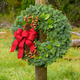 Holiday wreath with pine cones, faux autumn berries and a red linen bow on a base of noble, pine and salal greens on a post in field