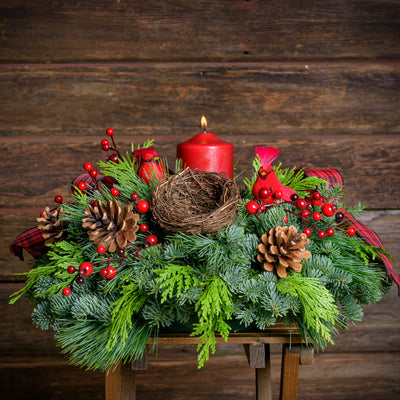 Fresh centerpiece of noble fir, cedar, pine with pine cones, red berries, red cardinal birds and red tartan bows
