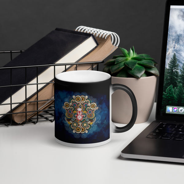 A magic mug with a colourful mandala pattern on a desk next to a laptop, and in front of some greenery.