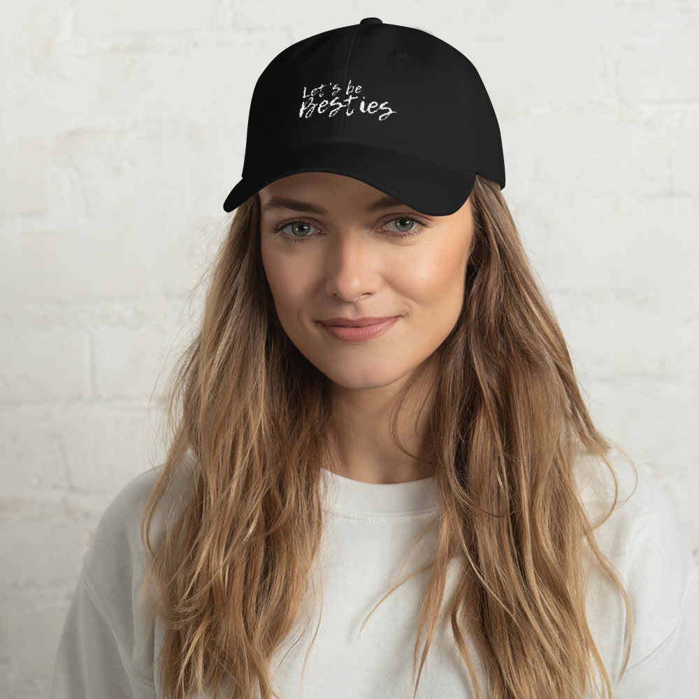A woman wearing a black cap that say Let's be Besties in white text.