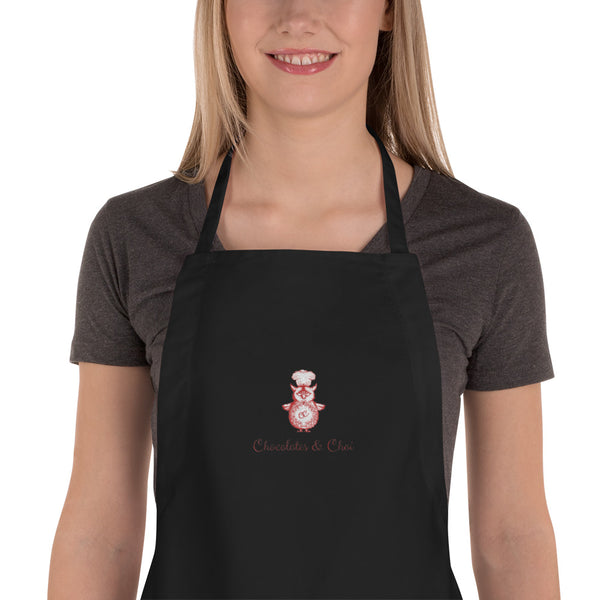 A close-up of a black apron with the Chocolates & Chai logo embroidered into the centre.