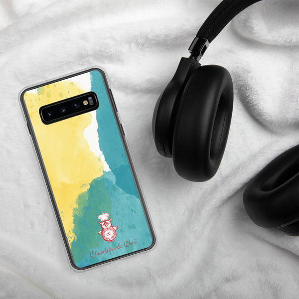 A sleek Samsung phone case with a yellow and green watercolour pattern and the red Chocolates & Chai owl logo, on a white blanket with headphones in the background.