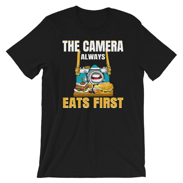 "A black t-shirt with a picture of a hungry camera eating a platter of food because ""The Camera Always Eats First"""