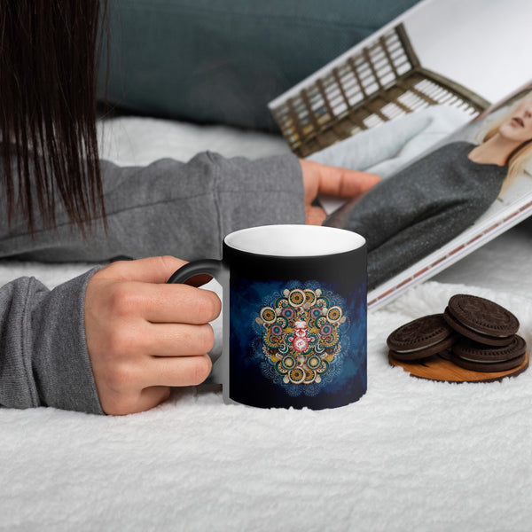 A magic mug with a colourful mandala pattern being held by someone reading a book.