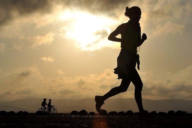 A Silhouette of a Woman Jogging. Endurance training.