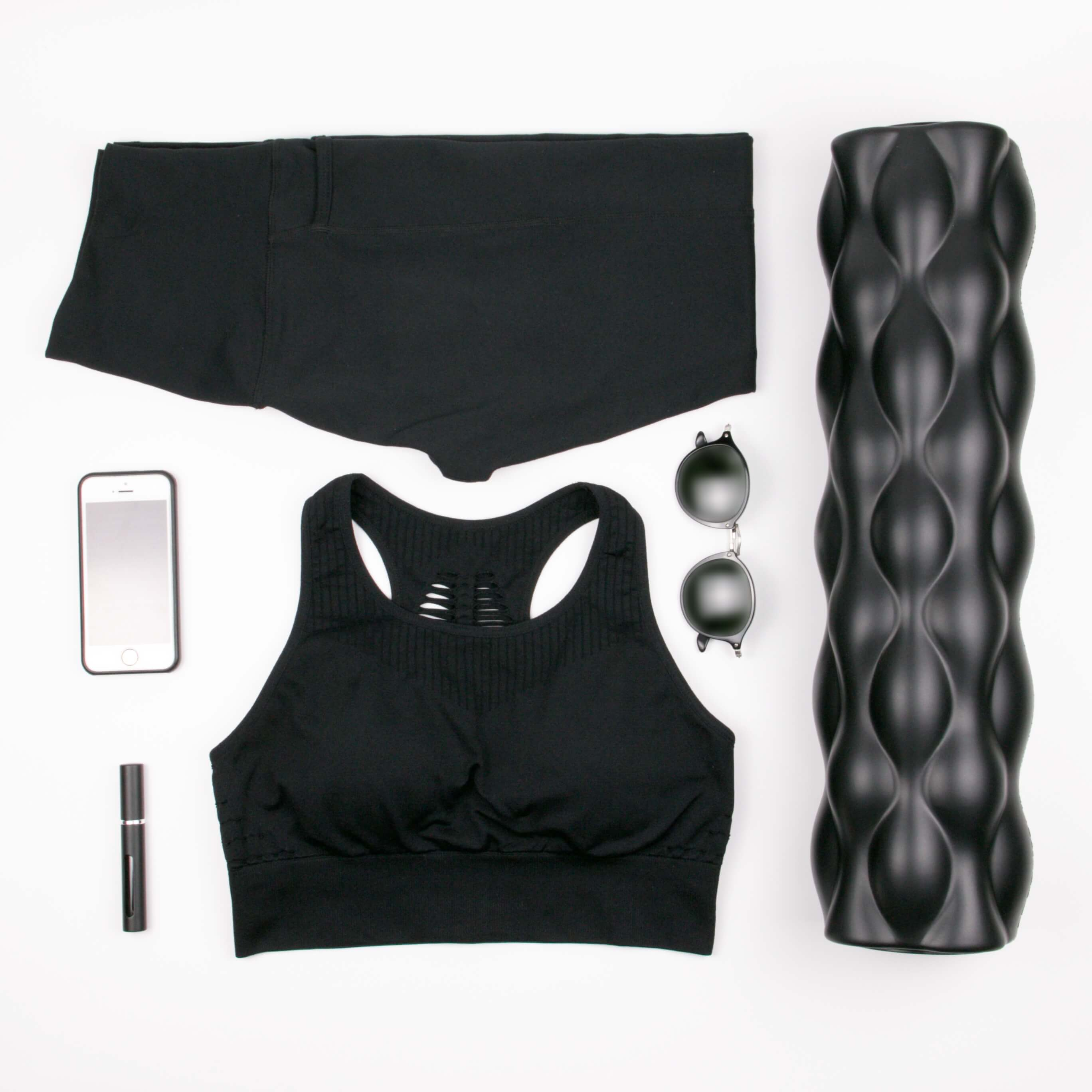 Gym clothes, foam roller, portable refillable atomizer all in black flat lay - Staying in Shape on Beach Vacation with these Must-Have Minimalist Fitness Items | Hummingbird