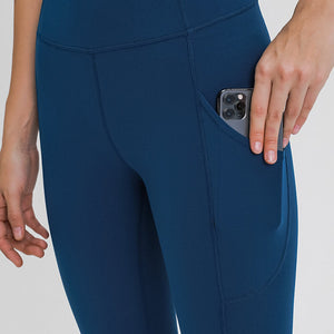 Carry your essentials with ease while you exercise in these Solid 7/8 Leggings with Pockets-Sapphire Blue. Featuring mid rise waistband and deep side pockets, these fitted workout leggings are perfect for jogging, yoga, weight training, and running errands. Side pockets can store essentials like a phone, keys, cards. Hidden waistband pocket in center back is another site for IDs or keys. Aesthetic seams accentuate body curves. Buttery soft fabric with a brushed feel enables performance even when it's cold.