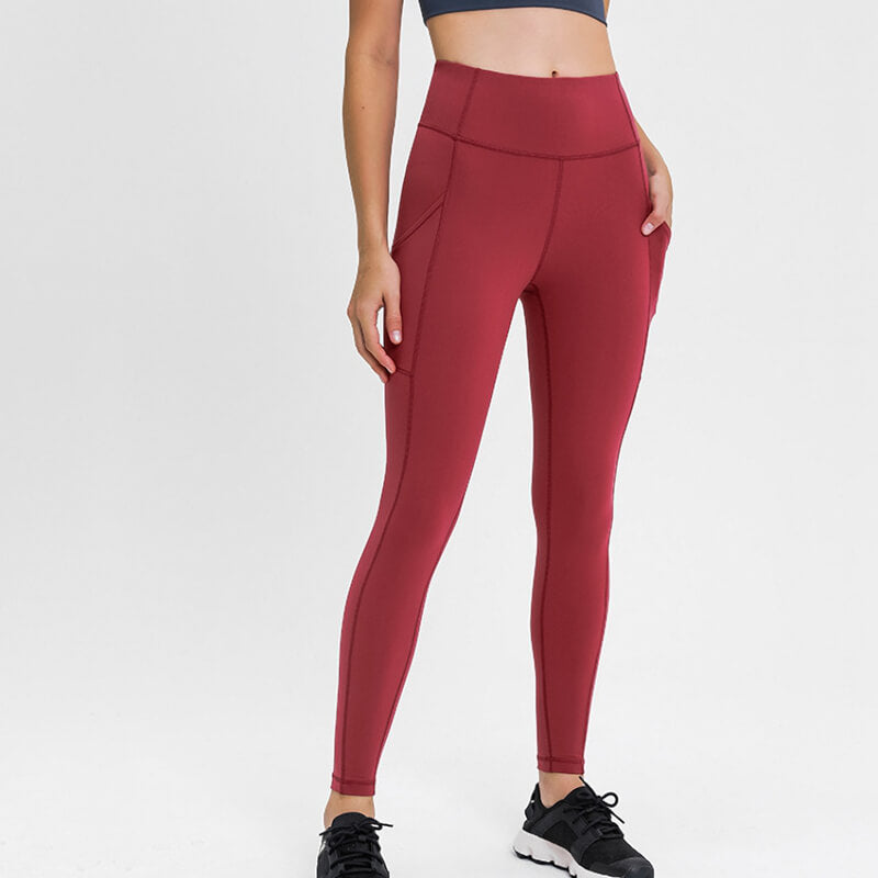 Carry your essentials with ease while you exercise in these Solid 7/8 Leggings with Pockets - Burgundy. Featuring mid rise waistband and deep side pockets, these fitted workout leggings are perfect for jogging, yoga, weight training, and running errands. Side pockets can store essentials like a phone, keys, cards etc. Hidden waistband pocket in center back is another site for IDs or keys. Aesthetic seams accentuate body curves. Buttery soft fabric with a brushed feel enables performance even when it's cold.