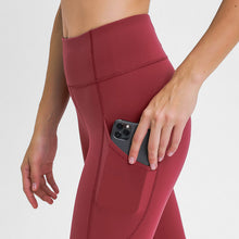 Load image into Gallery viewer, Carry your essentials with ease while you exercise in these Solid 7/8 Leggings with Pockets - Burgundy. Featuring mid rise waistband and deep side pockets, these fitted workout leggings are perfect for jogging, yoga, weight training, and running errands. Side pockets can store essentials like a phone, keys, cards etc. Hidden waistband pocket in center back is another site for IDs or keys. Aesthetic seams accentuate body curves. Buttery soft fabric with a brushed feel enables performance even when it's cold.