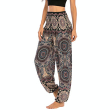 Load image into Gallery viewer, Empower your energy flow and blood circulation during yoga practice with these Bohemian Geometric Circle Mandala Yoga Harem Pants - Black. Featuring circle and geometric mandalas, these loose fitting yoga pants are the must-have companion for your yoga journey, be it for asanas, pranayama, or meditation. With high rise smocked waist and elastic ankles, these loose yoga pants can be adjusted to different styles. Handmade by Thai people with natural plant dye techniques. Also perfect for holiday travel.