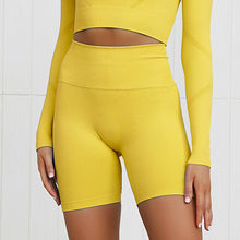 Load image into Gallery viewer, This Candy Scrunch Seamless Biker Shorts Set - Mango comes with a pair of high waisted booty scrunch biker shorts. Ruched detail on center chest echoes booty scrunch. Widened waistband lies flat against your skin and won't dig in, along with reinforcing underbutt panels and booty scrunch design, these biker shorts accentuate mid to lower body curves. Seamless fabrication reduces chafing and four-way stretch material is moisture-wicking. Perfect for all sorts of workout activities.