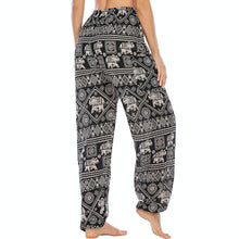 Load image into Gallery viewer, Featuring white elephants, geometric and floral elements, these Drawstring Elephant Diamond Loose Yoga Pants - Black are the must-have companion for your yoga journey, be it for asanas, pranayama, or meditation. With high rise smocked waist, elastic ankles and an adjustable drawstring, these loose yoga pants can be adjusted to fit most body types. Handmade with breathable, soft, lightweight and quick dry fabric and natural dyeing techniques. Perfect for yoga, meditation, dancing or vacations.
