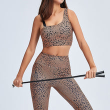 Load image into Gallery viewer, Make a purr-fect statement in this Feline Asymmetrical Sports Bra & Leggings Set - Lunar Blue. This matching workout set comes with a padded sports bra and a pair of leggings. Padded sports bra features asymmetrical shoulder straps. Leggings are mid-rise fitted. Stylish cheetah print shows your wild side in action. This 2 piece workout set is ideal for all sorts of activities from yoga to gym to street.