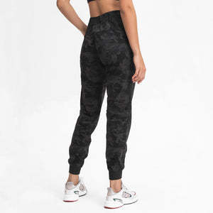 Keep yourself warm and mobile with these Loose Fit Pocket Drawstring Joggers in Black Camo. Featuring elasticated waistband with drawstring and loose fit silhouette, these athletic joggers can be worn alone or on top of leggings. Side pockets can store essentials like a phone or ID. Elasticated ribbed cuffs keep fabric in place and can be used to style different lengths. Perfect for in and out of the gym or studio, jogging, dancing and more.