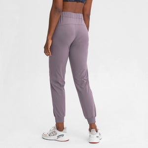 Keep yourself warm and mobile with these Loose Fit Pocket Drawstring Joggers in Mystic Purple. Featuring elasticated waistband with drawstring and loose fit silhouette, these athletic joggers can be worn alone or on top of leggings. Side pockets can store essentials like a phone or ID. Elasticated ribbed cuffs keep fabric in place and can be used to style different lengths. Perfect for in and out of the gym or studio, jogging, dancing and more.