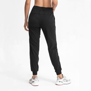 Keep yourself warm and mobile with these Loose Fit Pocket Drawstring Joggers in Black. Featuring elasticated waistband with drawstring and loose fit silhouette, these athletic joggers can be worn alone or on top of leggings. Side pockets can store essentials like a phone or ID. Elasticated ribbed cuffs keep fabric in place and can be used to style different lengths. Perfect for in and out of the gym or studio, jogging, dancing and more.