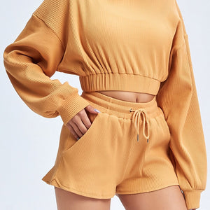 Keep yourself warm and mobile with this Move Free Ribbed Crop Top & Gym Short Set in Pumpkin Spice. Pullover long sleeve sweatshirt features cropped length, dropped shoulders, and elasticated ribbed hem. Matching gym shorts are mid-rise with drawstring. Side pockets can store essentials like a phone or ID. Elasticated ribbed cuffs keep fabric in place. Breathable ribbed cotton fabric empowers freedom of movement. Perfect for OOTD, outer wear pre/post gym or studio, jogging, dancing and more.