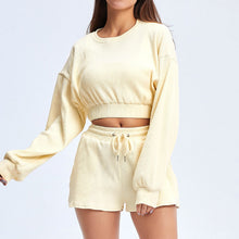 Load image into Gallery viewer, Keep yourself warm and mobile with this Move Free Ribbed Crop Top & Gym Short Set in Cream. Pullover long sleeve sweatshirt features cropped length, dropped shoulders, and elasticated ribbed hem. Matching gym shorts are mid-rise with drawstring. Side pockets can store essentials like a phone or ID. Elasticated ribbed cuffs keep fabric in place. Breathable ribbed cotton fabric empowers freedom of movement. Perfect for OOTD, outer wear pre/post gym or studio, jogging, dancing and more.