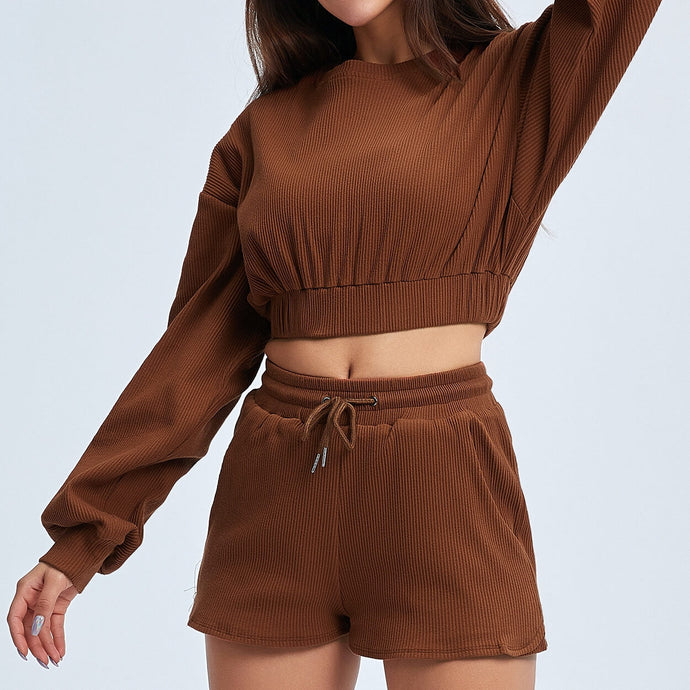 Keep yourself warm and mobile with this Move Free Ribbed Crop Top & Gym Short Set in Copper Brown. Pullover long sleeve sweatshirt features cropped length, dropped shoulders, and elasticated ribbed hem. Matching gym shorts are mid-rise with drawstring. Side pockets can store essentials like a phone or ID. Elasticated ribbed cuffs keep fabric in place. Breathable ribbed cotton fabric empowers freedom of movement. Perfect for OOTD, outer wear pre/post gym or studio, jogging, dancing and more.