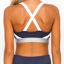 Load image into Gallery viewer, Hummingbird Navy Sports Set containing a Navy Sports Bra with a silver metallic band and elastic shoulder straps and a pair of Navy Striped Cropped Leggings with asymmetric blue and white stripes