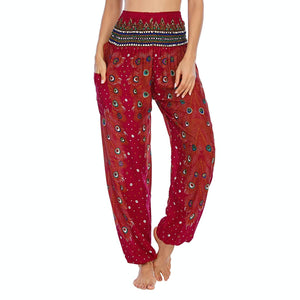 Empower your energy flow and blood circulation during yoga practice with these Hummingbird Peacock Smocked Waist Yoga Harem Pants - Burgundy. Featuring long peacock train feathers and colorful eyespots, these loose yoga pants are the must-have companion for your yoga journey, be it for asanas, pranayama, or meditation. Fit most body types with high rise smocked waist and elastic cuffed hems. Handmade by Thai people with breathable, soft, lightweight and quick dry fabric and natural dyeing techniques.