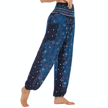 Load image into Gallery viewer, Empower your energy flow and blood circulation during yoga practice with these Hummingbird Peacock Smocked Waist Yoga Harem Pants - Navy. Featuring long peacock train feathers and colorful eyespots, these loose yoga pants are the must-have companion for your yoga journey, be it for asanas, pranayama, or meditation. Fit most body types with high rise smocked waist and elastic cuffed hems. Handmade by Thai people with breathable, soft, lightweight and quick dry fabric and natural dyeing techniques.