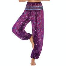 Load image into Gallery viewer, Empower your energy flow and blood circulation during yoga practice with these Hummingbird Peacock Smocked Waist Yoga Harem Pants - Magenta. Featuring long peacock train feathers and colorful eyespots, these loose yoga pants are the must-have companion for your yoga journey, be it for asanas, pranayama, or meditation. Fit most body types with high rise smocked waist and elastic cuffed hems. Handmade by Thai people with breathable, soft, lightweight and quick dry fabric and natural dyeing techniques.