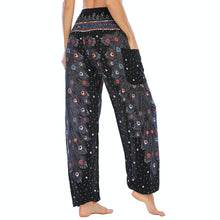 Load image into Gallery viewer, Empower your energy flow and blood circulation during yoga practice with these Hummingbird Peacock Smocked Waist Yoga Harem Pants - Black. Featuring long peacock train feathers and colorful eyespots, these loose yoga pants are the must-have companion for your yoga journey, be it for asanas, pranayama, or meditation. Fit most body types with high rise smocked waist and elastic cuffed hems. Handmade by Thai people with breathable, soft, lightweight and quick dry fabric and natural dyeing techniques.