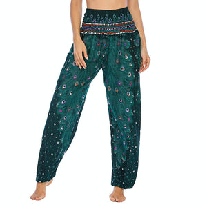 Empower your energy flow and blood circulation during yoga practice with these Hummingbird Peacock Smocked Waist Yoga Harem Pants - Teal Green. Featuring long peacock train feathers and colorful eyespots, these loose yoga pants are the must-have companion for your yoga journey, be it for asanas, pranayama, or meditation. Fit most body types with high rise smocked waist and elastic cuffed hems. Handmade by Thai people with breathable, soft, lightweight and quick dry fabric and natural dyeing techniques.