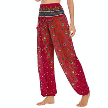 Load image into Gallery viewer, Empower your energy flow and blood circulation during yoga practice with these Hummingbird Peacock Smocked Waist Yoga Harem Pants - Burgundy. Featuring long peacock train feathers and colorful eyespots, these loose yoga pants are the must-have companion for your yoga journey, be it for asanas, pranayama, or meditation. Fit most body types with high rise smocked waist and elastic cuffed hems. Handmade by Thai people with breathable, soft, lightweight and quick dry fabric and natural dyeing techniques.