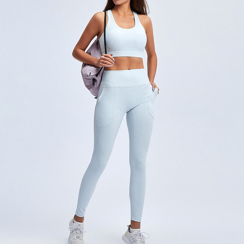 With this Ribbed Seamless Pocket Leggings & Sports Bra Set in Ice Blue, incorporating activewear into your everyday wardrobe is made easy. This matching workout set comes with a pair of leggings with pockets and a racerback sports bra. Leggings are mid-rise fitted with side pockets for essentials like a phone or an ID. Racerback sports bra features a scoop neckline. This cozy and textured 2 piece workout set is ideal for low to medium impact activities such as weight training and yoga.