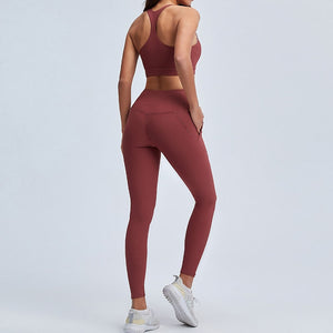 With this Ribbed Seamless Pocket Leggings & Sports Bra Set in Warm Red, incorporating activewear into your everyday wardrobe is made easy. This matching workout set comes with a pair of leggings with pockets and a racerback sports bra. Leggings are mid-rise fitted with side pockets for essentials like a phone or an ID. Racerback sports bra features a scoop neckline. This cozy and textured 2 piece workout set is ideal for low to medium impact activities such as weight training and yoga.