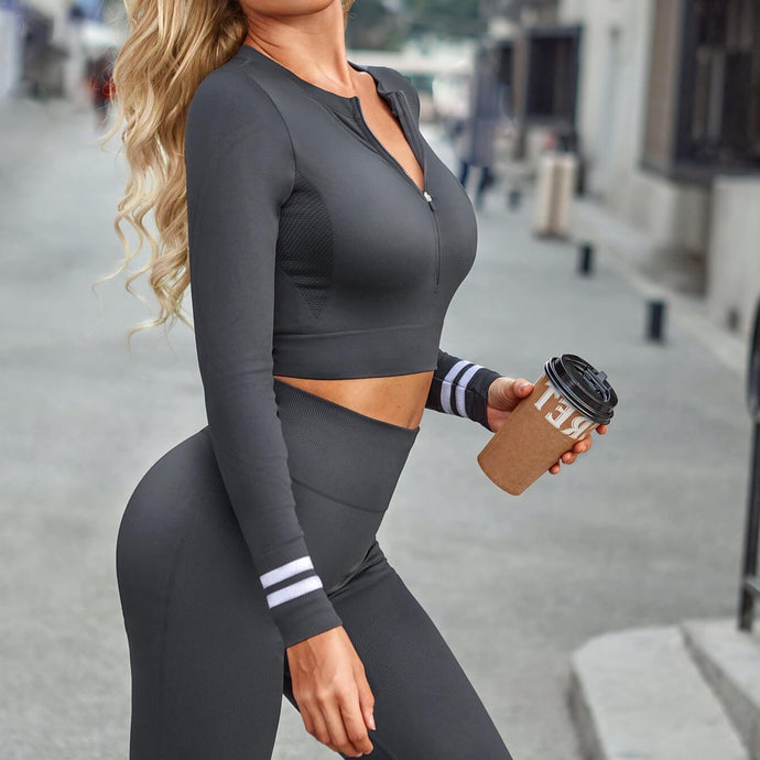Deliver a full-on foxy athletic look in this Seamless Front Zip Crop Top & Leggings Set - Charcoal. This matching workout set comes with a long sleeve crop top and a pair of leggings. Long sleeve crop top features zip up front and long ribbed cuffs with stripe details. Leggings are high-rise fitted with seamless front. This form-fitting 2 piece workout set is perfect for all sorts of activities from yoga to cardio to street.