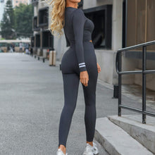 Load image into Gallery viewer, Deliver a full-on foxy athletic look in this Seamless Front Zip Crop Top & Leggings Set - Charcoal. This matching workout set comes with a long sleeve crop top and a pair of leggings. Long sleeve crop top features zip up front and long ribbed cuffs with stripe details. Leggings are high-rise fitted with seamless front. This form-fitting 2 piece workout set is perfect for all sorts of activities from yoga to cardio to street.