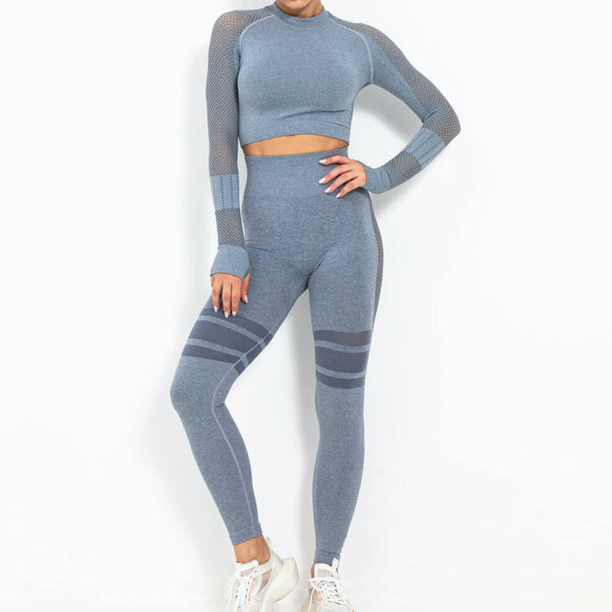Go bold and make a statement in this Seamless Side Mesh & Stripe Crop Top Leggings Set - Smoky Blue. High waisted leggings feature high rise side mesh originating just below waistband and symmetric stripes on mid-thigh. Extensive mesh panels and eyelets on saddle long sleeve crop top promote ventilation and along with thumbholes support your movements. This flattering matching workout set is perfect for all sorts of workout activities.