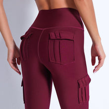 Load image into Gallery viewer, Style your gym to street look with these Solid High Waist Cargo Leggings - Burgundy. Workout leggings with side pockets can be very useful when you want to bring your phone with you during workout, be it for a tracking fitness app, or music on the phone. These fitted cargo leggings feature four flap pockets - two on the sides and two on the back, for essentials like a phone, keys, cards etc. These capris leggings are breathable and non-see-through. Also perfect for post-gym errand running.