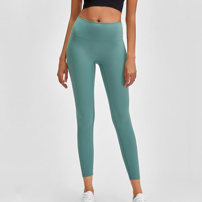 Enjoy a next to skin feel in these Solid Minimalist 7/8 Leggings in Teal Green. These fitted workout leggings have minimal flatlock seams that minimize chafing during workout and elongate the appearance of your legs. Widened mid to high rise waistband lies flat against your skin and won't dig in. Buttery soft material with a brushed feel is breathable, moisture-wicking and dries quickly. Perfect for yoga, weight training, jogging, as well as running errands and lounging.