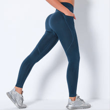 Load image into Gallery viewer, Bring Your Electronic Companion Along with this Solid Pocket Leggings & Plunge Sports Bra Set - Midnight Blue. This workout set includes a pair of leggings and a sports bra. High waisted leggings feature a slim right side pocket and contouring ribbed panels. Right side pocket can store essentials like a phone, keys, cards etc. Plunge sports bra has two adjustable thin straps that can attach to each other, forming a crisscross.