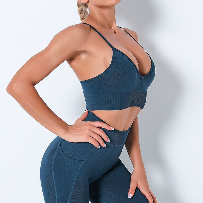 Bring Your Electronic Companion Along with this Solid Pocket Leggings & Plunge Sports Bra Set - Midnight Blue. This workout set includes a pair of leggings and a sports bra. High waisted leggings feature a slim right side pocket and contouring ribbed panels. Right side pocket can store essentials like a phone, keys, cards etc. Plunge sports bra has two adjustable thin straps that can attach to each other, forming a crisscross.