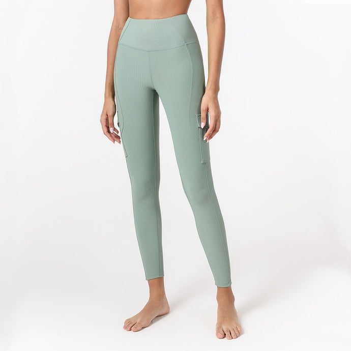 Complete the studio to street look with these Solid Ribbed High Waist Cargo Leggings - Mystic Lake. Featuring high rise waistband, two patch pockets with flaps on side of thigh, these fitted workout leggings are perfect for yoga, weightlifting, jogging and more, as well as running errands. Cargo pockets can store essentials like a phone, keys, cards etc. Aesthetic seams accentuate body curves. Soft and lightweight material with ribbed design is breathable and moisture-wicking.