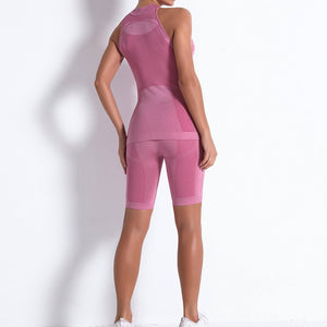 Necessitate self-discipline with this Solid Seamless Cosmo Tank & Biker Shorts Set - Pink. This matching workout set includes a tank top and a pair of biker shorts. Individual items are available for mixing and matching. Tank top has a high neck and is snugly fitted, supporting your movement as the final layer no matter what exercise you are engaging in. Biker shorts are high-waist fitted with above the knee length. Extensive and aesthetic ribbed panels accentuate your hard effort through self-discipline.