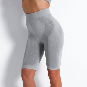 Necessitate self-discipline with this Solid Seamless Cosmo Tank & Biker Shorts Set - Grey. This matching workout set includes a tank top and a pair of biker shorts. Tank top has a high neck and is snugly fitted, supporting your movement as the final layer no matter what exercise you are engaging in. Biker shorts are high-waist fitted with above the knee length. Extensive and aesthetic ribbed panels accentuate your hard effort through self-discipline.