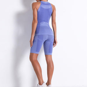 Necessitate self-discipline with this Solid Seamless Cosmo Tank & Biker Shorts Set - Blue. This matching workout set includes a tank top and a pair of biker shorts. Individual items are available for mixing and matching. Tank top has a high neck and is snugly fitted, supporting your movement as the final layer no matter what exercise you are engaging in. Biker shorts are high-waist fitted with above the knee length. Extensive and aesthetic ribbed panels accentuate your hard effort through self-discipline.