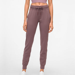 These Solid Slim Fit Drawstring Joggers - Pale Purple are great for either in studio, at the gym, work at home or on the go. Featuring mid-rise, slim fit and adjustable drawstring, these cuffed joggers are as versatile as they are comfortable. Open deep pockets can store essentials like a phone, keys, cards etc. Buttery soft material is breathable, moisture-wicking and dries quickly. Perfect for yoga, cardio, jogging as well as errand running and lounging. Complete the look with a crop top or crop tank.
